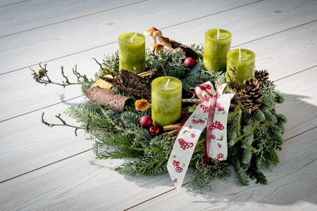 Advent krans van takjes met groene kaarsen en diverse ornamenten