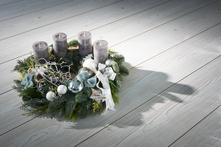 Advent wreath of twigs with grey candles and various ornaments photo