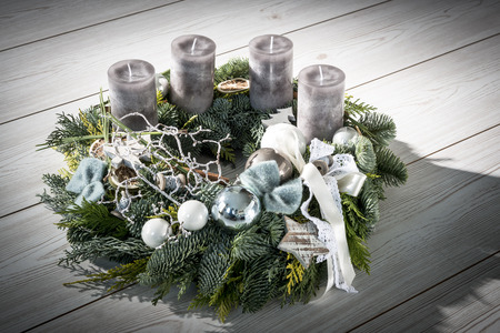 Advent wreath of twigs with grey candles and various ornaments