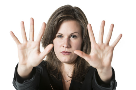 both: Business woman in black suit holds both hand up to stop someone or something, isolated on white background