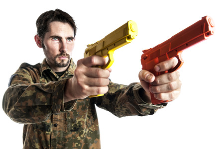 Male self defense instructor with camouflage do a self defense exercise with training gun, isolated on white background photo