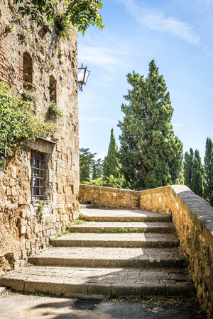 Small street with stairs in Pienza Tuscany, Italy in summer with blue sky