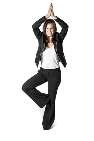 Business woman in black suit performs a yoga exercise on white background