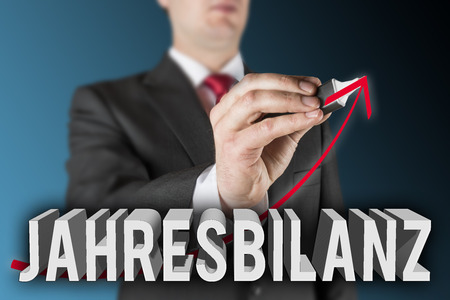 Lettering of the German word Jahresbilanz with business man is drawing an increasing arrow photo