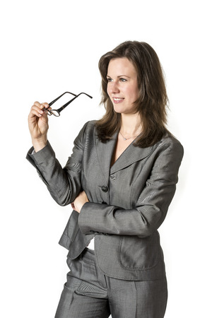 Picture of a laughing business woman holding glasses in a gray suit isolated on white background photo