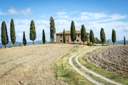 Landscape in Tuscany, italy with house, fields, cypresses and blue sky photo