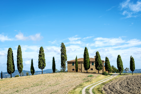 agriturismo: Landscape in Tuscany, italy with house, fields, cypresses and blue sky