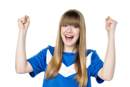 Happy girl in blue soccer shirt is holding her fists up photo