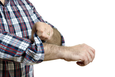 Man in a plaid shirt rolls up his sleeves, isolated on white background