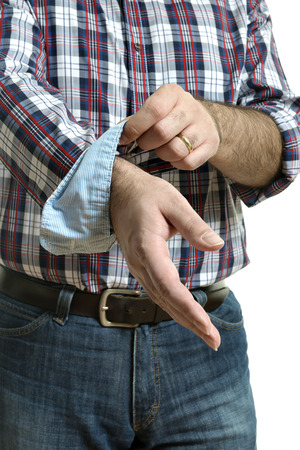 his shirt sleeves: Man in jeans and a plaid shirt rolls up his sleeves, isolated on white background Stock Photo
