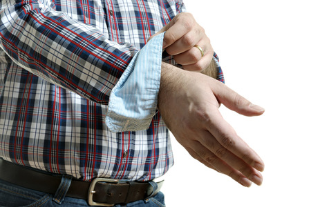 Man in jeans and a plaid shirt rolls up his sleeves, isolated on white background photo
