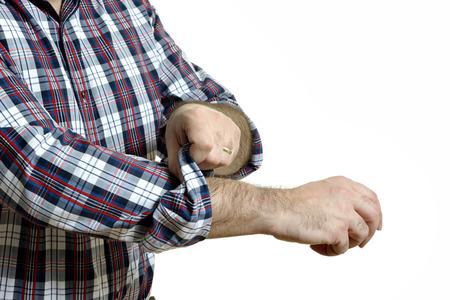 格子縞のシャツの男が白い背景に分離された彼の袖をロールします。