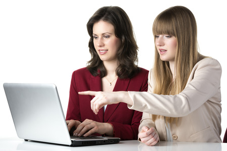 Two happy women blonde and brunette, sitting together in front of a laptop photo