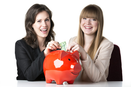 Two happy women sitting at a table and throwing 100 euro in a red piggy bank photo