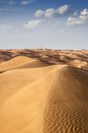 Desert Wahiba in Oman with clouds on blue sky photo