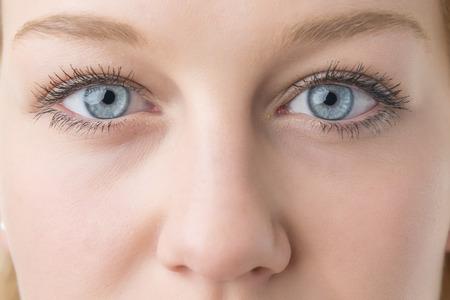 Close-up van jonge blonde vrouw met blauwe ogen en neus Stockfoto
