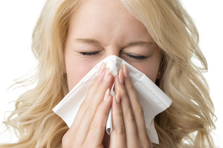Portrait of a ill blond woman who is sneezing in a tissue photo