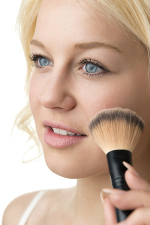 Closeup makeup applying of a blond woman photo