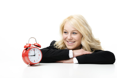Laughing blond woman with red alarm clock photo
