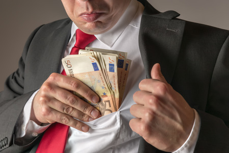 Businessman in dark suit and with tie putting money in his pocket photo
