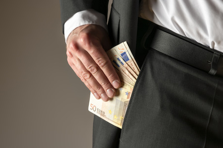 putting money in pocket: Businessman in dark suit and with tie putting money in his pocket
