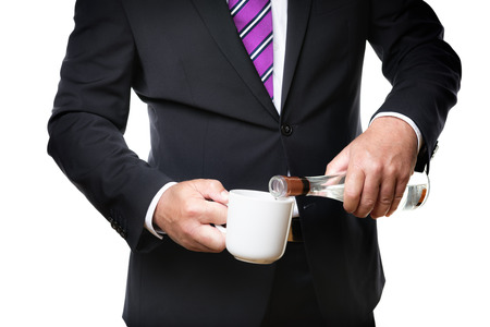 Business man in dark suite with a coffee cup and a bottle with alcohol photo
