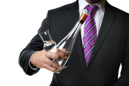 grappa: Business man in dark suite with a grappa glas and a bottle with alcohol Stock Photo