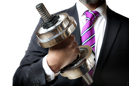 Businessman in black suit holding a silver dumbbell in the right hand Stockfoto