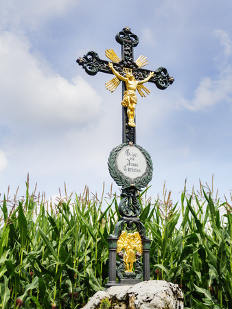 praised: Wrought iron wayside cross with lettering  Praised be Jesus Christ  in German language