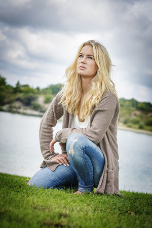 Blond woman kneeling on a grean meadow at the edge of a lake in summer