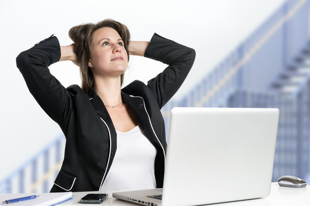 Image of a business woman sitting at her desk dreaming photo