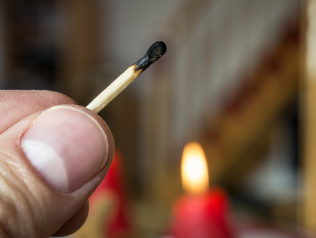 advent candles: Picture of an extinct match with candles in the background