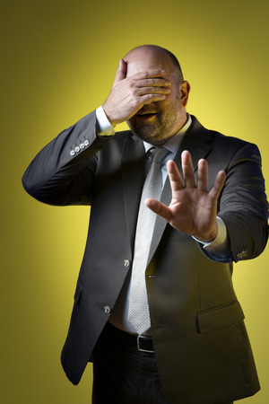 Stressed businessman in dark suit holding up hand in front of his eyes and parries with the other hand, against yellow background photo