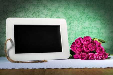 blank slate: Image of a blank slate blackboard on a wooden table with pink roses