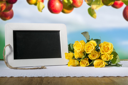 blank slate: Image of a blank slate blackboard on a wooden table with yellow roses and apples in background
