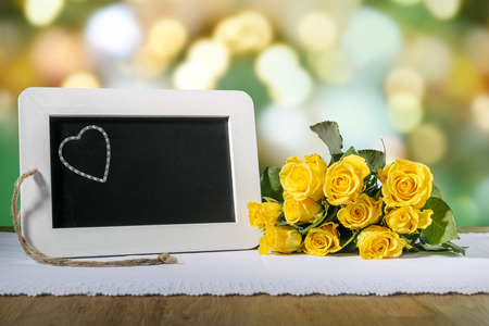 Image of a slate blackboard with heart on a wooden table with yellow roses photo