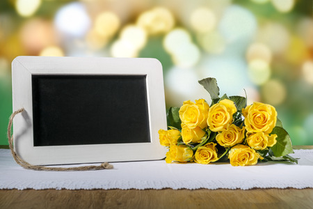 blank slate: Image of a blank slate blackboard on a wooden table with yellow roses Stock Photo