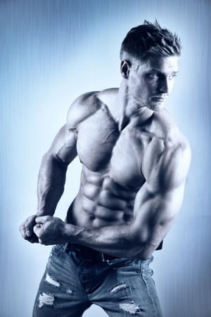 pectoral: Posing young well trained man with perfect abdominal and pectoral muscle on blue metal background Stock Photo