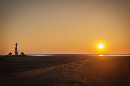 westerhever: Image of a sunset on the dike of Westerhever in Northern Germany with lighthouse and free space in the sky