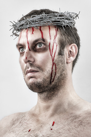 tortured: Portrait of a bleeding man tortured with a crown of barbed wire. Stock Photo