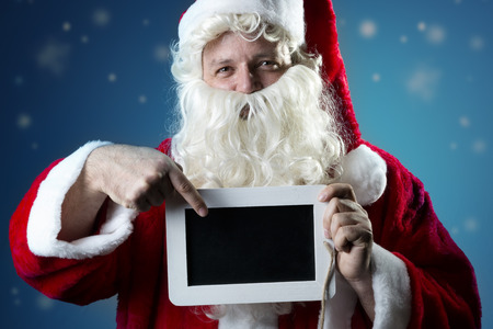 blank slate: Image portrait of Santa Claus in red coat with snow pointing a finger on a blank slate