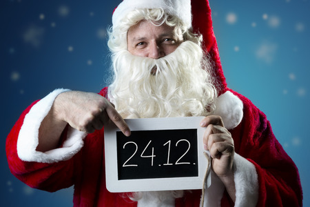 blank slate: Santa Claus pointing a finger on a blank slate with text Merry Christmas Stock Photo