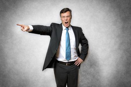 怒っているビジネス スーツを着て、叫んで、指で指している男の画像