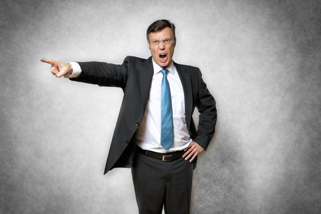 image of angry business man in suit who is screaming and pointing with finger