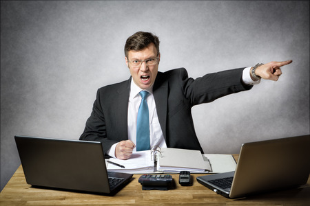 image of angry business man in suit who is screaming and pointing with finger in his office