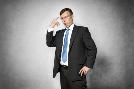 Image of conceited business man in dark suit pointing his finger to his head