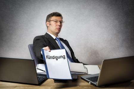 Baas zitten aan de balie in kantoor te ontslaan iemand met Duitse papieren