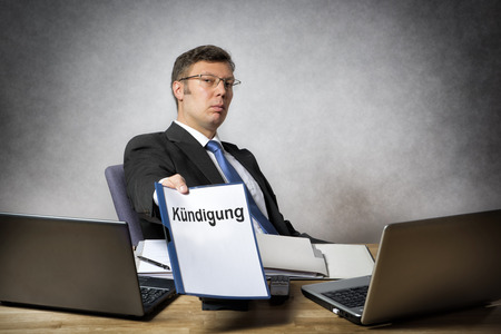 dismiss: Boss sitting at the desk in office dismiss somebody with german paper