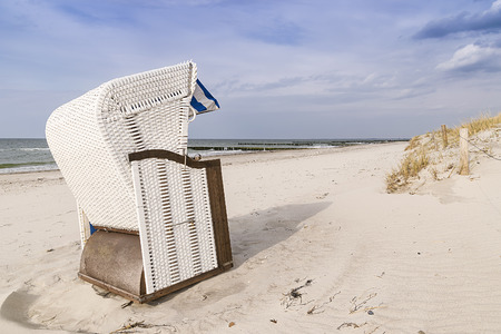 Picture of a beach chair on the Baltic Sea beach with dune grass and sea in the background