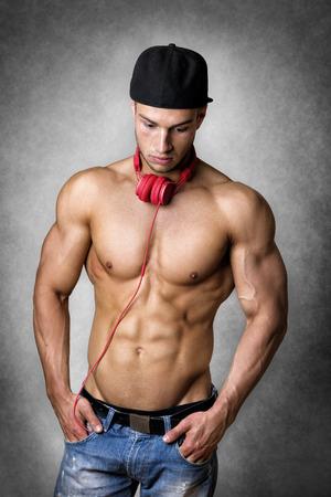 abdominal fitness: Hombre reflexivo joven con el cuerpo bien entrenado con una gorra de b�isbol y pantalones de mezclilla Foto de archivo
